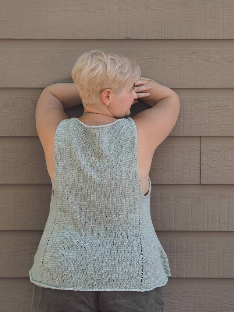 white woman in blue knitted tank leaning against a wall with her back to the camera
